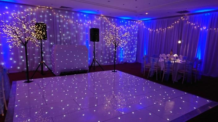 winter wonderland christmas parties at the portsmouth marriott white led dancefloor backdrop light up trees and full room drape