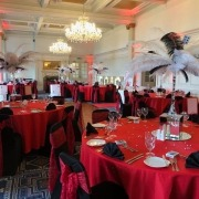 queens hotel portsmouth vegas casino tablecloth with black and white feather centerpiece on mirror box styling black chair cover and red lace sash 4